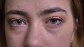 Πορτρέτο κινηματογραφήσεων σε πρώτο πλάνο του νέου όμορφου καυκάσιου θηλυκού προσώπου με τα πράσινα μάτια που εξετάζουν ευθέα τη  φιλμ μικρού μήκους