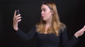 Πορτρέτο κινηματογραφήσεων σε πρώτο πλάνο του νέου όμορφου καυκάσιου θηλυκού που έχει μια τηλεοπτική κλήση στο τηλέφωνο που μιλά  απόθεμα βίντεο