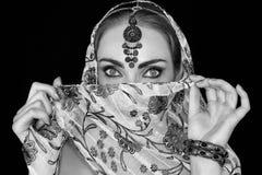 Πορτρέτο μιας ασιατικής νέας γυναίκας σε ένα μαντίλι με μια διακόσμηση και των κοσμημάτων σε γραπτό στοκ φωτογραφία