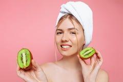 Πορτρέτο μιας ελκυστικής εύθυμης γυναίκας με μια πετσέτα που τυλίγεται γύρω από το κεφάλι της, που κρατά τις φέτες ακτινίδιων πέρ στοκ φωτογραφίες με δικαίωμα ελεύθερης χρήσης