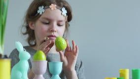 Πορτρέτο μιας μαθήτριας με μια βούρτσα και τα χρώματα που διακοσμεί ένα αυγό Πάσχας Χριστιανικές παραδόσεις, έννοια Πάσχας φιλμ μικρού μήκους