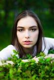 Πορτρέτο μιας όμορφης νέας γυναίκας σε ένα υπόβαθρο των πράσινων φύλλων, καλοκαίρι υπαίθρια Φυσικά όμορφη γυναίκα που χαμογελά εν στοκ εικόνες