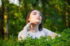 Πορτρέτο μιας όμορφης νέας γυναίκας σε ένα υπόβαθρο των πράσινων φύλλων, καλοκαίρι υπαίθρια Φυσικά όμορφη γυναίκα που χαμογελά εν στοκ φωτογραφία