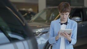 Πορτρέτο της βέβαιας όμορφης γυναίκας στην επίσημη ένδυση που χρησιμοποιεί την ταμπλέτα της που ελέγχει τα αυτοκίνητα στη έκθεση  απόθεμα βίντεο