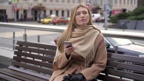 Πορτρέτο της κομψής συνεδρίασης γυναικών σε έναν πάγκο με την τηλεφωνική αναμονή φιλμ μικρού μήκους