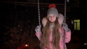 Πορτρέτο της μικρής όμορφης οδήγησης κοριτσιών αργά στην ταλάντευση και του χαμόγελου ήρεμα στη κάμερα στο υπόβαθρο χειμερινών οδ απόθεμα βίντεο