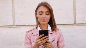 Πορτρέτο της νέας γυναίκας που χρησιμοποιεί το smartpone απόθεμα βίντεο