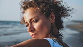 Πορτρέτο της νέας όμορφης στάσης γυναικών στην παραλία και του κοιτάγματος στη θάλασσα στοκ εικόνα