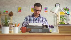 Πορτρέτο της δακτυλογράφησης συγγραφέων νεαρών άνδρων με την έμπνευση σε μια παλαιά γραφομηχανή απόθεμα βίντεο