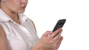 Πορτρέτο της όμορφης γυναίκας που χρησιμοποιεί το smartphone στο άσπρο υπόβαθρο φιλμ μικρού μήκους