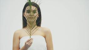 Πορτρέτο της όμορφης νέας γυναίκας με το φυσικό makeup και του τροπικού φύλλου στο άσπρο υπόβαθρο απόθεμα βίντεο