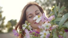 Πορτρέτο της όμορφης νέας γυναίκας που χαμογελά και που κρατά την ανθοδέσμη των άγριων λουλουδιών φιλμ μικρού μήκους