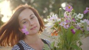 Πορτρέτο της όμορφης νέας γυναίκας που χαμογελά και που κρατά την ανθοδέσμη των άγριων λουλουδιών απόθεμα βίντεο