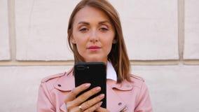Πορτρέτο της όμορφης νέας γυναίκας που χρησιμοποιεί το smartphone απόθεμα βίντεο