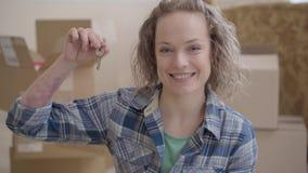 Πορτρέτο της χαριτωμένης γυναίκας στο ελεγμένο πουκάμισο που παρουσιάζει κλειδί από το κοίταγμα σπιτιών κεκλεισμένων των θυρών με απόθεμα βίντεο