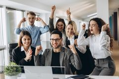Πορτρέτο της πολύ ευτυχούς επιτυχούς εκφραστικής gesturing επιχειρησιακής ομάδας στο γραφείο στοκ εικόνες