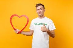 Πορτρέτο του ευτυχούς ατόμου στην άσπρη μπλούζα με τη γραπτή επιγραφή πράσινος τίτλος εθελοντική λαβή μεγάλη κόκκινη ξύλινη καρδι στοκ εικόνα