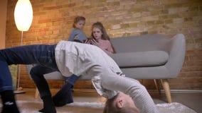 Πορτρέτο του μικρού καυκάσιου κοριτσιού που κάνει μια γέφυρα με τις αδελφές της στο υπόβαθρο απόθεμα βίντεο
