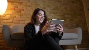 Πορτρέτο του νέου καυκάσιου κοριτσιού με την κυματιστή συνεδρίαση τρίχας στην προσοχή πατωμάτων smilingly στην ταμπλέτα χαρωπά στ φιλμ μικρού μήκους