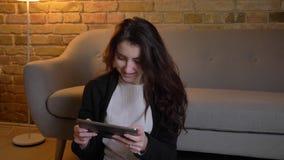 Πορτρέτο του νέου καυκάσιου κοριτσιού με την κυματιστή συνεδρίαση τρίχας στην προσοχή πατωμάτων ευχάριστα στην ταμπλέτα χαρωπά στ απόθεμα βίντεο