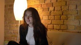 Πορτρέτο του νέου καυκάσιου κοριτσιού με την κυματιστή τρίχα που προσέχει τη TV με το ευχάριστο ενδιαφέρον στο άνετο εγχώριο υπόβ απόθεμα βίντεο