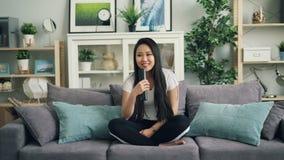 Πορτρέτο του όμορφου ασιατικού κοριτσιού που χρησιμοποιεί τη συνεδρίαση τηλεχειρισμού στον καναπέ στο σπίτι και τη TV προσοχής πε φιλμ μικρού μήκους