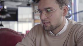 Πορτρέτο του όμορφου ατόμου που ανατρέχει κάτω στο σύγχρονο καφέ κοντά Ο μοντέρνος βέβαιος επιχειρηματίας κινεί το κεφάλι του στο απόθεμα βίντεο