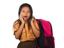 Πορτρέτο του όμορφου ευτυχούς και συγκινημένου κοριτσιού στη φέρνοντας τσάντα σπουδαστών σχολικών στολών που χαμογελά εύθυμο που  στοκ εικόνα