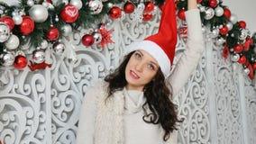 Πορτρέτο του όμορφου νέου brunette στο κόκκινο καπέλο santa που χαμογελά και που κοιτάζει στη κάμερα στο στούντιο φιλμ μικρού μήκους