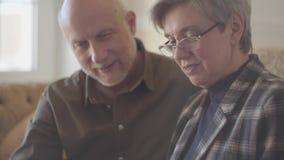 Πορτρέτο του ώριμων ζεύγους, του άνδρα και της γυναίκας, που κάθονται στον καναπέ με ένα βιβλίο και που μιλούν και που χαμογελούν φιλμ μικρού μήκους