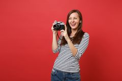 Πορτρέτο του χαμόγελου της αρκετά νέας γυναίκας στα ριγωτά ενδύματα που κρατά την αναδρομική εκλεκτής ποιότητας κάμερα φωτογραφιώ στοκ εικόνα