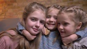 Πορτρέτο τριών μικρών καυκάσιων κοριτσιών που αγκαλιάζουν το ένα το άλλο ευτυχώς στην άνετη εγχώρια ατμόσφαιρα φιλμ μικρού μήκους
