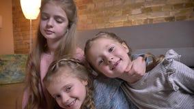 Πορτρέτο τριών μικρών καυκάσιων κοριτσιών που αγκαλιάζουν το ένα το άλλο χαρωπά στην άνετη εγχώρια ατμόσφαιρα απόθεμα βίντεο