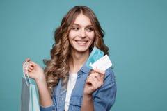Πορτρέτο τσαντών των χαρωπών όμορφων κοριτσιών εκμετάλλευσης αγορών και παρουσίαση πιστωτικών καρτών στοκ φωτογραφία με δικαίωμα ελεύθερης χρήσης