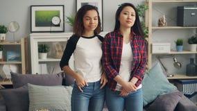 Πορτρέτο των όμορφων νέων γυναικών Ασιάτης και του αφροαμερικάνου που στέκονται στο σπίτι μαζί, της εξέτασης τη κάμερα και του χα φιλμ μικρού μήκους