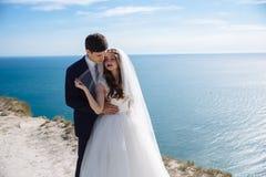 Πορτρέτο των newlyweds στη ημέρα γάμου στον απότομο βράχο με την όμορφη άποψη του ωκεανού στοκ φωτογραφίες με δικαίωμα ελεύθερης χρήσης