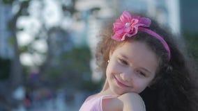 Πορτρέτο χαριτωμένο λίγο καυκάσιο θηλυκό παιδιών, παιδί υπαίθρια σε ένα ρόδινο φόρεμα με ένα ρόδινο λουλούδι σε επικεφαλής της, ό απόθεμα βίντεο