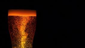 Ποτήρι κινηματογραφήσεων σε πρώτο πλάνο της μπύρας με τη δίνη δομών και της αύξησης επάνω στις αεροφυσαλίδες γύρω από τη ζωτικότη απόθεμα βίντεο