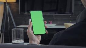 Πράσινη οθόνη - άτομο που κρατά ένα smartphone Πέρα από την όψη ώμων απόθεμα βίντεο