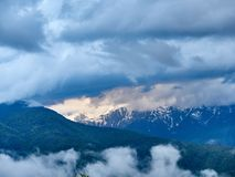 Πράσινο δάσος στο υπόβαθρο των υψηλών χιονωδών βουνών στοκ εικόνες
