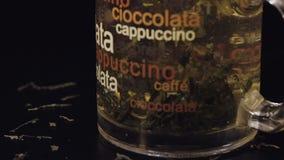 πράσινο τσάι Προσθήκη της φέτας του λεμονιού στο φλυτζάνι γυαλιού με τα οργανικά ξηρά πράσινα φύλλα τσαγιού απόθεμα βίντεο