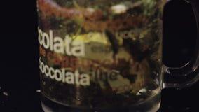 πράσινο τσάι Προσθήκη της φέτας του λεμονιού στο φλυτζάνι γυαλιού με το οργανικό ξηρό πράσινο τσάι φιλμ μικρού μήκους