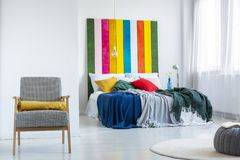 Πραγματική φωτογραφία ενός φωτεινού εσωτερικού κρεβατοκάμαρων με τους άσπρους τοίχους, τη comfy πολυθρόνα και τα ζωηρόχρωμα καλύμ στοκ εικόνες