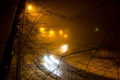Προβολείς αυτοκινήτων σε μια ομιχλώδη νύχτα στοκ φωτογραφία