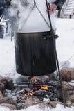 Προετοιμασία τροφίμων στο τεράστιο μαύρο κύπελλο στη φωτιά στο χειμώνα στοκ εικόνες με δικαίωμα ελεύθερης χρήσης