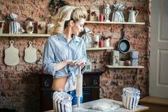 Προκλητικός νέος ξανθός ερωτικός γυναικών προετοιμάζει τη ζύμη στην κουζίνα νοικοκυρά με τις τσάντες του αλευριού και με την κυλώ στοκ φωτογραφία με δικαίωμα ελεύθερης χρήσης