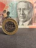 προσέγγιση στο νόμισμα της ενός εξαιρετικών λίβρας και υποβάθρου με το αυστραλιανό τραπεζογραμμάτιο είκοσι δολαρίων