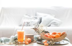 Πρόσφατα-αυξημένος οργανικός φρέσκος χυμός από πορτοκάλι στο εσωτερικό του σπιτιού, με ένα τυρκουάζ κάλυμμα και ένα καλάθι των φρ στοκ φωτογραφίες