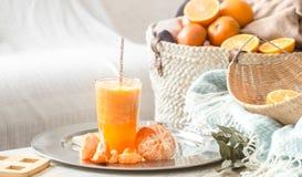 Πρόσφατα-αυξημένος οργανικός φρέσκος χυμός από πορτοκάλι στο εσωτερικό του σπιτιού, με ένα τυρκουάζ κάλυμμα και ένα καλάθι των φρ στοκ εικόνες