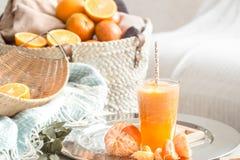 Πρόσφατα-αυξημένος οργανικός φρέσκος χυμός από πορτοκάλι στο εσωτερικό του σπιτιού, με ένα τυρκουάζ κάλυμμα και ένα καλάθι των φρ στοκ εικόνα με δικαίωμα ελεύθερης χρήσης